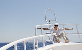 A man in bright clothes wearing a cap and glasses on a yacht stock image