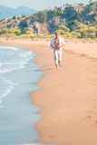 Man in bright clothing runs. Along the beach line Royalty Free Stock Image