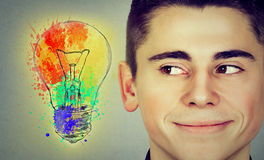 Man with bright idea light bulb looking sideways smiling Royalty Free Stock Images