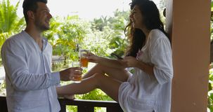 Man bring juice to young woman use cell smart phone sitting on balcony, happy smiling couple talking on summer terrace. In tropical hotel slow motion 60 stock footage