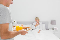 Man bringing breakfast in bed to his partner. At home in bedroom Royalty Free Stock Images