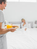 Man bringing breakfast in bed to his surprised partner Royalty Free Stock Photography