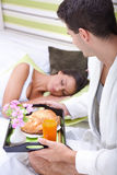 Man bringing the breakfast his girlfriend. To in bed Royalty Free Stock Photo