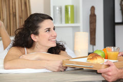 Man bringing breakfast to girlfriend Royalty Free Stock Photos