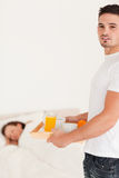 Man bringing breakfast to his sleeping wife Royalty Free Stock Photos