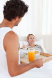 Man bringing the breakfast to his wife Royalty Free Stock Image