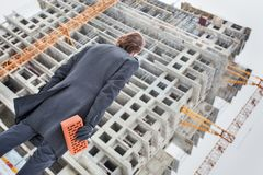 Personal contribution to construction. Man is bringing brick to the construction site to make a personal contribution. Personal investments, contribution to Royalty Free Stock Images