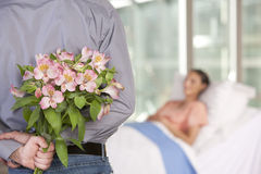 Man bringing flowers to patient Royalty Free Stock Images