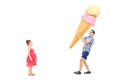 Man bringing huge ice cream to excited girl Royalty Free Stock Photos