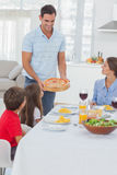 Man bringing a pizza to his family Royalty Free Stock Image