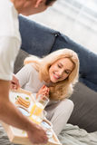 Man bringing tray with tasty breakfast to happy blonde woman Royalty Free Stock Images