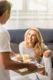 Man bringing tray with tasty breakfast to happy blonde woman Stock Photos