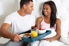 Man Bringing Woman Breakfast In Bed On Tray. Smiling To Each Other Stock Photography