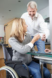 Man Bringing Woman In Wheelchair Hot Drink At Home Royalty Free Stock Photos