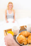 Man bringing young attractive woman breakfast in bed Stock Images