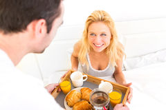 Man bringing young attractive woman breakfast in bed Stock Photo