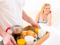 Man bringing young attractive woman breakfast in bed Royalty Free Stock Photography