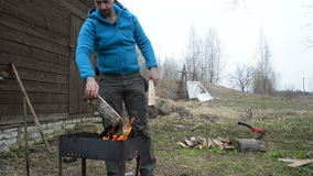 Man brings firewood from birch and kindles a fire in a brazier Stock Photos