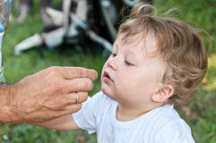 Man brings to the child's mouth hand Stock Photo