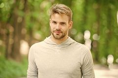 Man with bristle on calm face, nature background, defocused. Skin care concept. Man with beard or unshaven guy looks. Handsome outdoor. Guy bearded and stock image