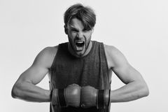 Man with bristle and furious face wears boxing gloves. Boxer makes hits and punches as training. Sports and competition. Concept. Athlete with leather box stock photos