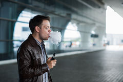 Man with a bristle smoking e-cigarette vaporizer box mode outdoors near the airport terminal before flight Stock Images
