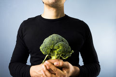 Man with broccoli. Detail of young man holding a head of broccoli Royalty Free Stock Photography
