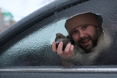 Man broke the glass of the car a little stone. Vandalism winter man broke the glass of the car a little stone Royalty Free Stock Photos