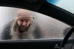 Man broke the glass of the car a little stone. Vandalism winter man broke the glass of the car a little stone Royalty Free Stock Photo
