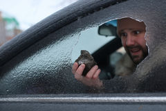 Man broke the glass of the car a little stone. Vandalism winter man broke the glass of the car a little stone Stock Photo