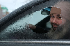 Man broke the glass of the car a little stone. Vandalism winter man broke the glass of the car a little stone Stock Photography