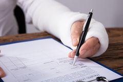 Man With Broken Arm Filling Health Insurance Claim Form. Close-up Of A Businessperson With Broken Arm Filling Health Insurance Claim Form On Wooden Desk stock images