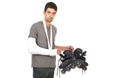 Man with broken arm holding rollerskating Royalty Free Stock Photography