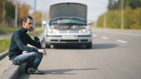 Man with broken car calling for help. Road trip car trouble. A young man with a silver car that broke down on the road stock footage