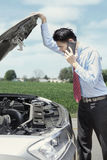 Man with broken car on highway Stock Images