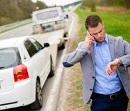 Man and broken car on a roadside. Man calling while tow truck picking up his broken car Royalty Free Stock Photo