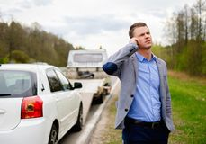 Man and broken car on a roadside. Man calling while tow truck picking up his broken car Royalty Free Stock Image