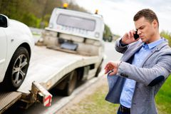 Man and broken car on a roadside. Man calling while tow truck picking up his broken car Royalty Free Stock Images