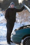 Man with broken car in winter. Man stands next to broken car in winter Royalty Free Stock Image