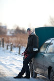 Man with broken car in winter. Man stands next to broken car in winter with accumulator wires Stock Photography