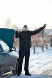 Man with broken car in winter. Man need help with his car stands with accumulator wires Royalty Free Stock Photos