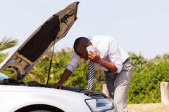 Man broken down car. Young man with broken down car with bonnet open calling for help Stock Images