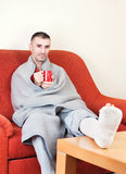 Man with broken leg. Man with a broken leg on a sofa at home holding cup of coffee royalty free stock image