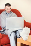 Man with broken leg. Man with a broken leg on a sofa at home working on laptop royalty free stock image