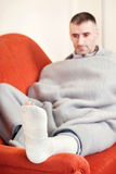 Man with broken leg. Man with a broken leg on a sofa at home royalty free stock images
