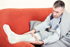 Man with broken leg. Man with a broken leg on a sofa at home having pain royalty free stock images