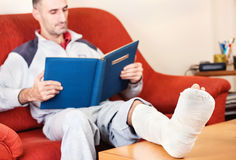 Man with broken leg. Man with a broken leg on a sofa at home reading book; focus on cast stock photography