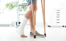 Man with broken leg in cast standing on crutches. Indoors stock photography