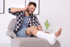 Man with broken leg in cast talking on mobile phone. While sitting in armchair at home stock images