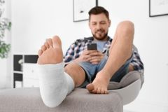 Man with broken leg in cast using mobile phone. While sitting in armchair at home stock photography